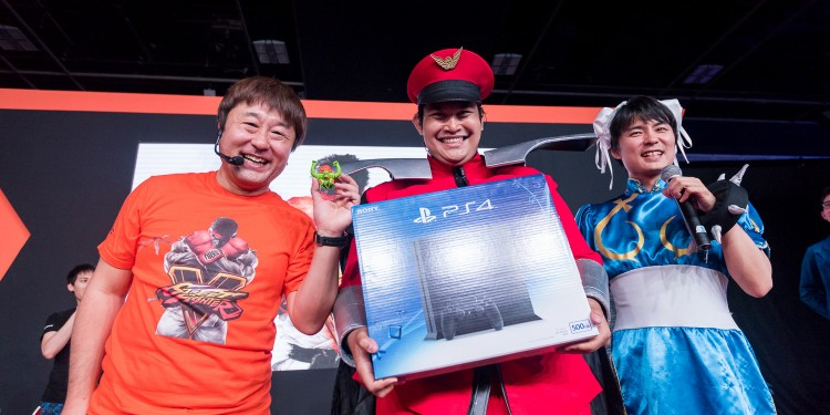 Capcom's Yoshinori Ono, Tomoaki Ayano and a lucky PS4 winner dressed as Street Fighter character M Bison
